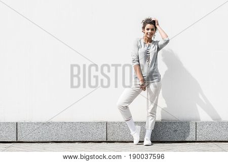 In good mood. Full length portrait of cheerful stylish young curly girl is holding hand near face and smiling while feeling glad. Copy space in the left side