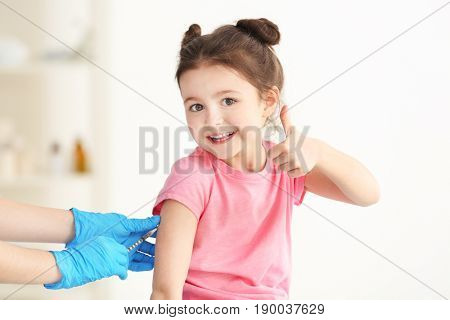 Vaccination concept. Female doctor vaccinating cute little girl in clinic
