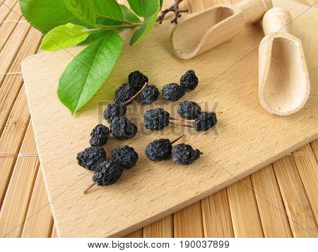 Dried aronia berries on wooden board and fresh leaves