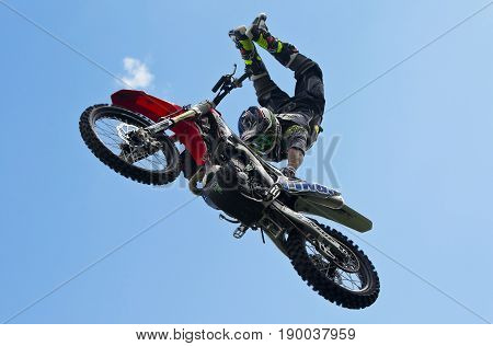 WEEDON, UK - AUGUST 27: A member of an FMX display team gives a riding and stunt demonstration to the watching crowd at the Bucks County show on August 27, 2015 in Weedon