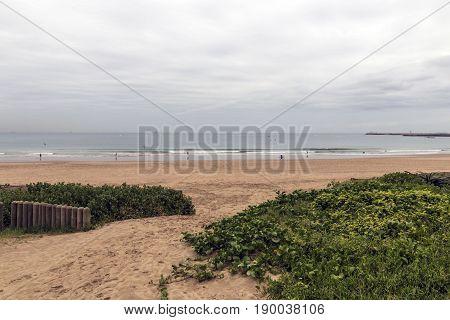 Sand pathway between dune vegetation entrance onto beach against coastal skyline in Durban South Africa