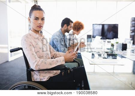 Portrait of businesswoman using digital tablet while sitting on wheelchair at creative office
