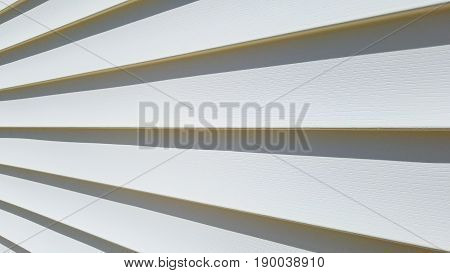 A closeup of outside white vinyl siding shadows.