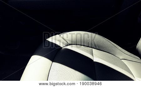 A black leather car bucket seat with a shadow across it.