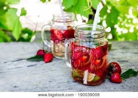 Fresh red strawberry lemonade in mason jar on a wooden table Against the background of grapevines. Summer drinks and cocktails