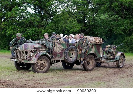 DENMEAD, UK - MAY 25: An ex WW2 German army light truck and AA gun site themselves in the main arena for the upcoming battle re-enactment at the Overlord show on May 25, 2014 in Denmead