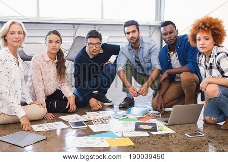 Portrait of creative business team working together on floor at office