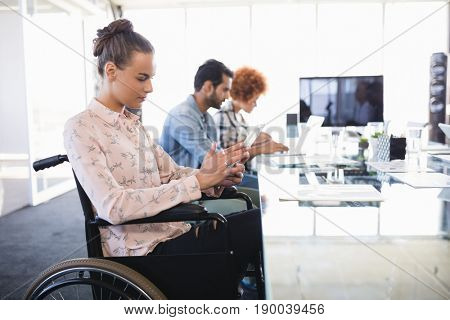 Businesswoman using digital tablet while sitting on wheelchair at creative office