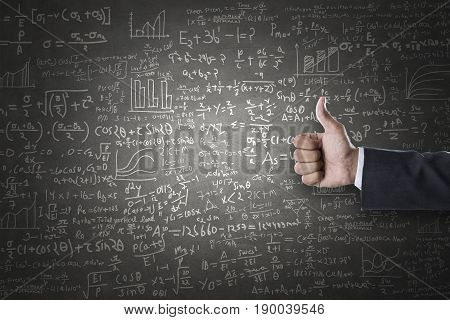 Women hand thumbs up sign in front of mathematical formulas drawn on blackboard