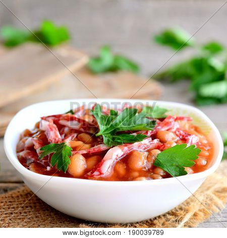 Smoked sausage and white bean stew. Simple white bean stew with smoked sausage, tomato sauce and fresh parsley in a bowl and on a wooden old table. Homemade nutritious stew. Closeup