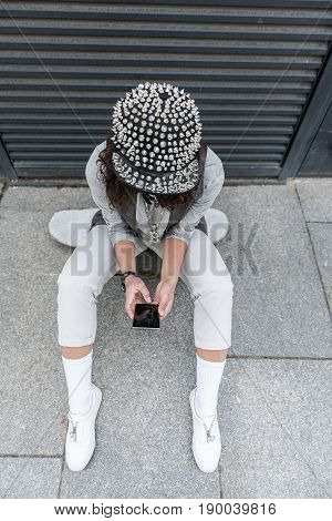 Always in touch. Top view of young hipster woman is wearing spike cap and sitting on skateboard while looking at screen of her smartphone