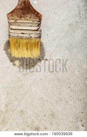 Housework renovation objects concept. Old dirty paint brush making wet splash on white concrete wall.