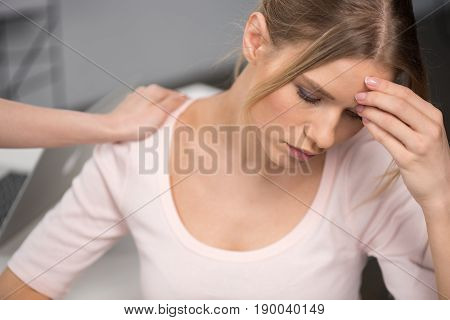 Cropped Shot Of Person Supporting Upset Young Woman Sitting With Hand On Forehead And Thinking