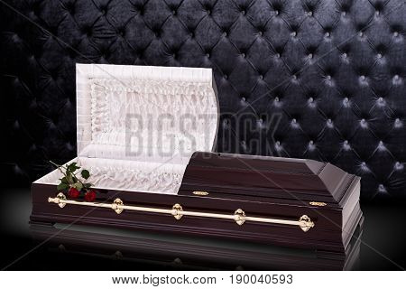 Opened wooden brown sarcophagus with a red roses isolated on gray luxury background. casket, coffin on royalbackground. Ritual objects for burial. Conduct of the deceased on his last journey. Surrender body dust of the earth. Christian funeral ritual