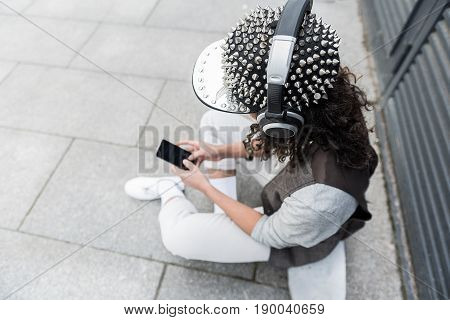 Enjoy your favorite song. Top view of young hipster woman sitting on skateboard on street and looking at screen of her smartphone while choosing record. Focus on spike cap with headphones