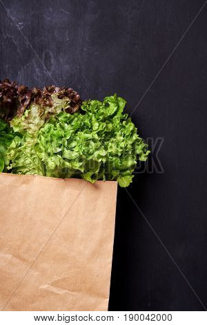 salad in paperbag on wooden background. top view