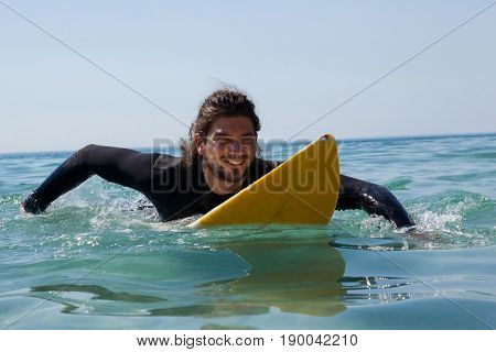 Smiling surfer surfboarding in the sea on a sunny day
