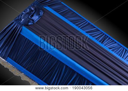 closed blue coffin covered with elegant cloth isolated on gray background. coffin close-up on royal background. Ritual objects for burial. Surrender body dust of the earth. Christian funeral ritual