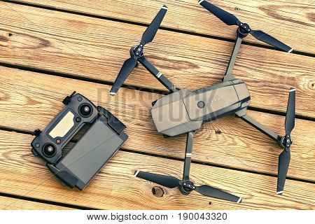 Drone quadcopter with a flight controller over wooden background. Top view flat lay