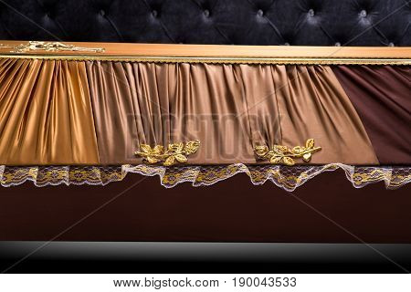 closed brown coffin covered with cloth isolated on gray background. coffin close-up on royal background. Ritual objects for burial. Surrender body dust of the earth. Christian funeral ritual