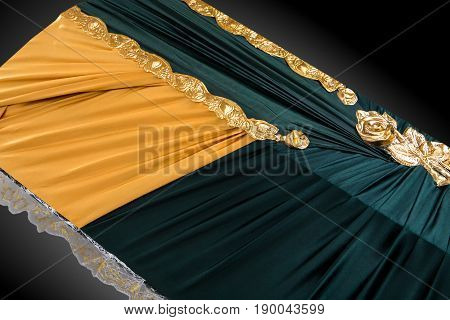 closed green and beige coffin covered with cloth isolated on gray background. coffin close-up with gold flowers on royal background. Ritual objects for burial. Surrender body dust of the earth. Christian funeral ritual