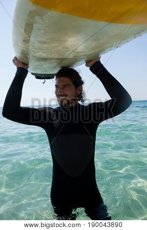 Smiling surfer in wetsuit carrying surfboard over head at beach coast
