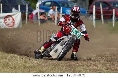 PUTTENHAM, UK - JULY 14: An unnamed rider competing in the Puttenham grasstrack racing event rides the top corner apex of the circuit at speed on July 14, 2013 in Puttenham