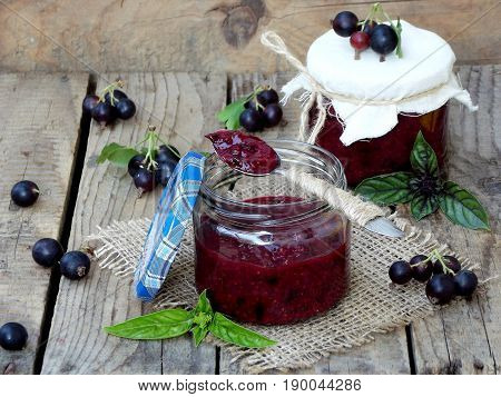 Two Jars Of Jam From The Black Currant On A Wooden Background. Berries Frayed With Sugar
