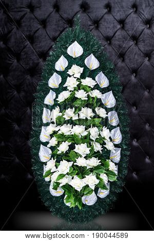 Luxury Funeral wreath with white flowers isolated on royal dark background. Ritual object for funeral