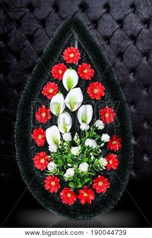 Luxury Funeral wreath with red and white flowers isolated on royal dark background. Ritual object for funeral