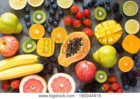 Different rainbow colored fruits on the grey concrete background, top view, selective focus