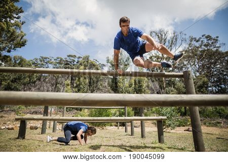 Man and woman jumping over the hurdles during obstacle course in boot camp