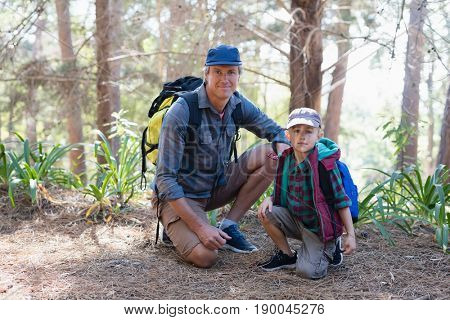 Portrait of mature father and elementary son kneeling in forest