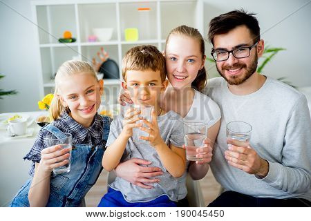 Happy family drinks water for breakfast in morning at home