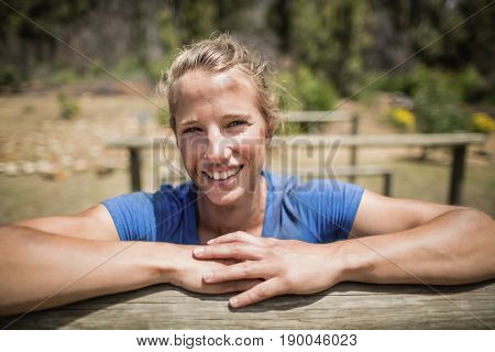 Smiling woman leaning on a hurdle during obstacle course in boot camp