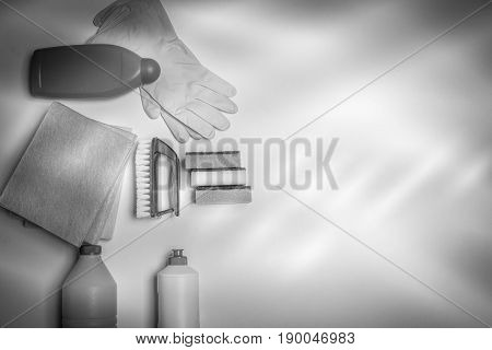 Range of cleaning products for the kitchen and bath. Detergents, chemical bottles, cleaning sponges and gloves. On a wooden table. view from above. Black and white filter.