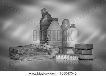 Range of cleaning products for the home. Detergents, chemical bottles, cleaning sponges and gloves. Black and white filter.