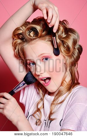 Portrait of a pretty girl teenager with curlers in her blonde hair and brushes. Teen style, fashionable teen girl. Cosmetics and make-up.