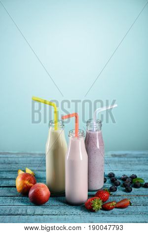 Homemade Fruity Milkshakes In Glass Bottles With Straws And Fresh Ingredients On Tabletop On Blue