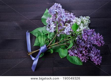 beautiful small bouquet of lilacs tied with a ribbon. A beautiful wooden background.