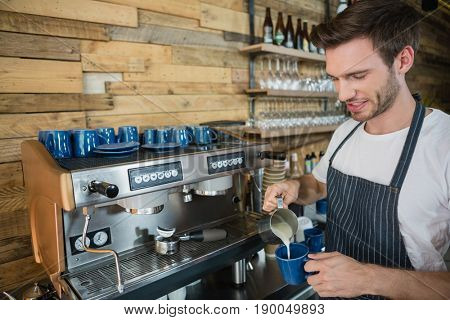 Waiter making coffee at counter in café