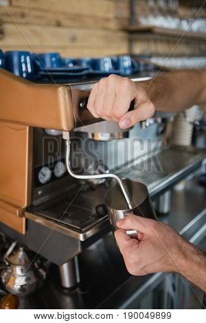Close-up of waiter hands pouring milk in jug from coffee machine in café