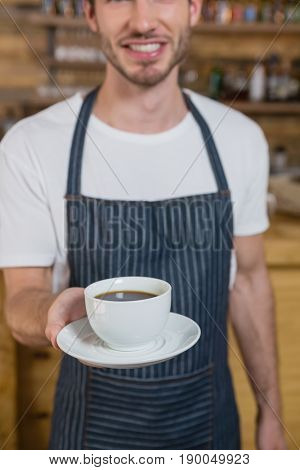 Smiling waiter offering cup of coffee in café