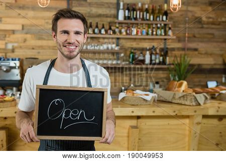 Portrait of smiling waiter standing with open signboard at counter in counter
