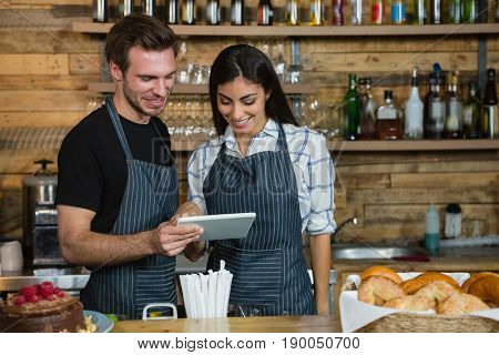 Waiter and waitresses using digital tablet at counter in café