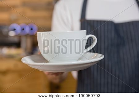 Mid section of waiter offering cup of coffee in café