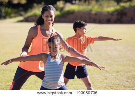Portrait of happy female trainer and girl practicing Virabhadrasana II pose at park