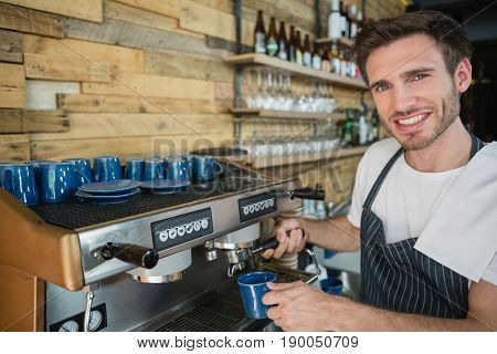 Portrait of smiling waiter preparing coffee from coffee machine in café