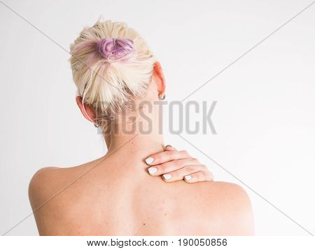 Young woman with nape pain hold her nape