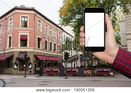 Man's hand with a smartphone on a background of city restaurant in Europe.  White screen, you can insert your own image or text here.